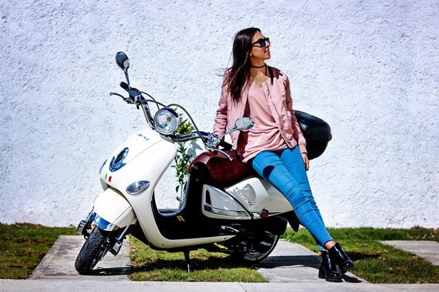 Žena v slnečných okuliaroch opretá o motorku.jpg