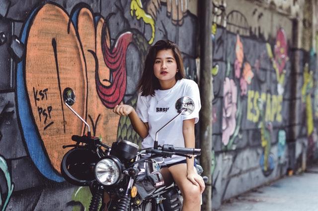 Žena v bielom tričku sedí na motorke.jpg