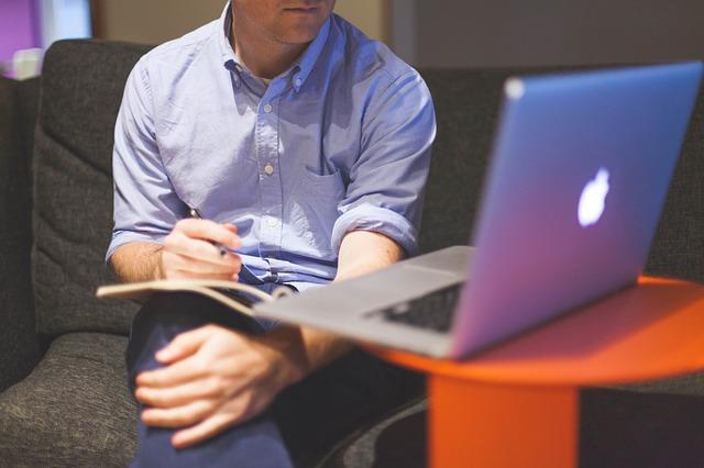 Muž v modrej košeli sedí na pohovke s zošitom na kolenách a pozerá o počítača.jpg