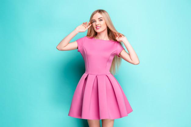 smiling-beautiful-young-woman-pink-mini-dress-posing-studio_155003-14602